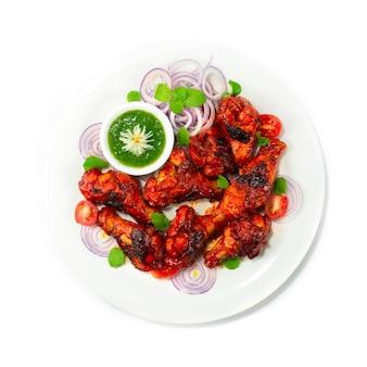 탄두리 치킨 그릴 드 민트 소스는 크리미 한 요거트베이스에 닭 날개를 담그고 양파와 야채 탑 뷰로 장식 된 혼합 향신료로 만든 고전적인 인도식 저녁 식사입니다.