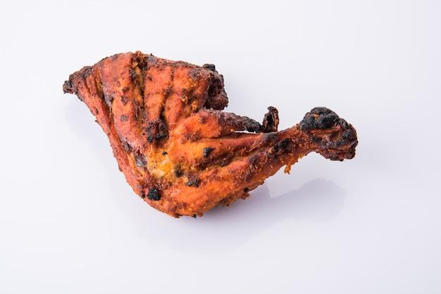 Цыпленок тандури - готовится путем запекания в тандыре курицы, маринованной в йогурте и специях. кусок ноги подается в тарелке с салатом на красочном или деревянном фоне. выборочный фокус