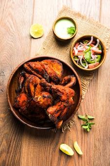 Цыпленок тандури - готовится путем запекания в тандыре курицы, маринованной в йогурте и специях. кусочки ножек подаются в тарелке с салатом и чатни