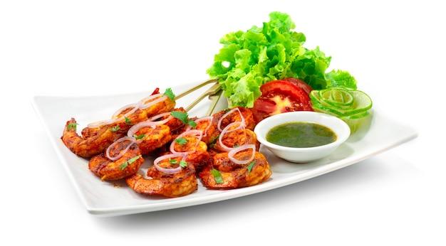 탄두리 새우 구이 꼬치 구이 민트 소스는 크림 같은 요구르트베이스에 새우 날개를 담그고 양파, 라임, 야채 사이드 뷰로 장식 한 혼합 향신료로 만든 고전적인 인도식 저녁 식사입니다.