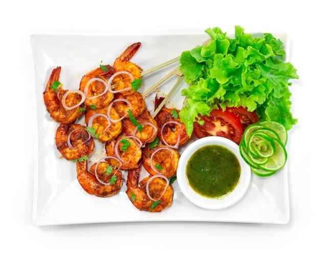 탄두리 새우 꼬치 구이 민트 소스는 크리미 한 요구르트베이스에 새우 날개를 담그고 양파, 라임, 야채 탑 뷰로 장식 한 혼합 향신료로 만든 고전적인 인도식 저녁 식사입니다.