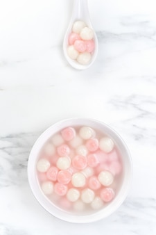 Тан юань, танъюань, вкусные красные и белые рисовые шарики с клецками в небольшой миске, вид сверху, плоская планировка. азиатская праздничная еда для фестиваля зимнего солнцестояния.