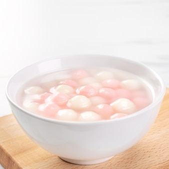 Tang yuan, tangyuan, delicious red and white rice dumpling balls in a small bowl. asian traditional festive food for chinese winter solstice festival, close up.