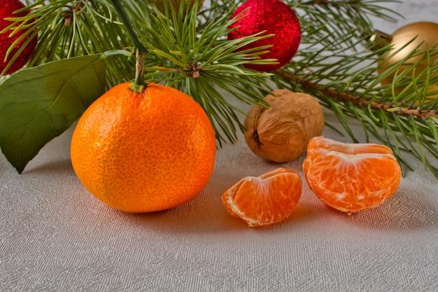 Мандарин и грецкий орех возле хвойной ветки. сочные дольки мандарина на столе возле елки.