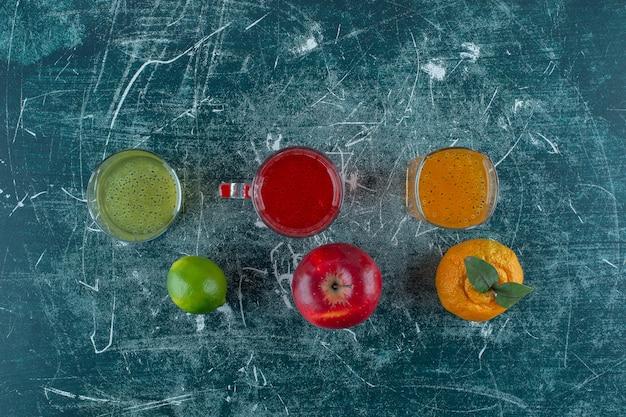파란색 테이블에 귤 사과, 레몬, 그리고 그들의 주스.