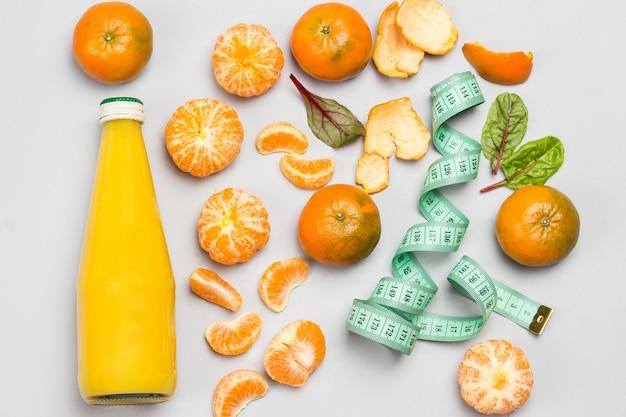 みかんの果実、ボトルに入った柑橘類のジュース、巻尺。灰色の背景。フラットレイ。