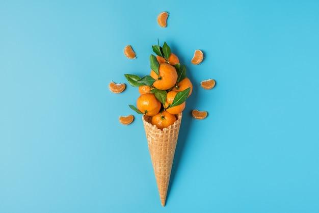 青い背景の上のワッフルアイスクリームコーンのタンジェリンフルーツ。冬のクリスマス料理のコンセプト。上面図。フラットレイ