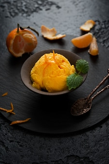 Tangerine ice cream in a cup, sorbet on a black background,