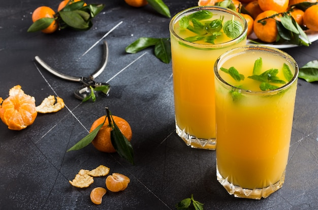 Tangerine juice in glasses on dark