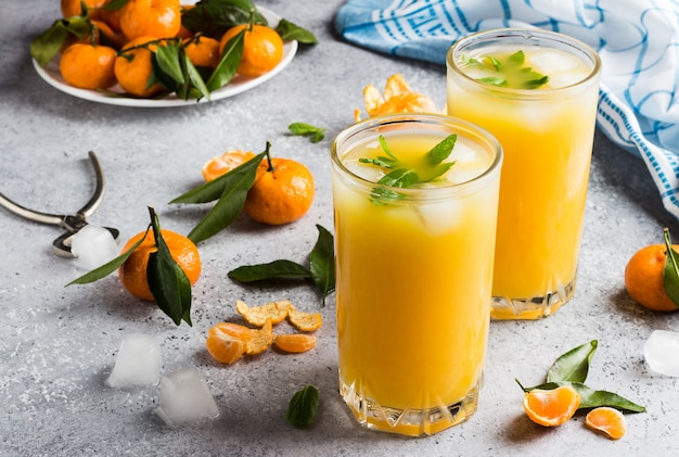 Tangerine juice in glasses on light