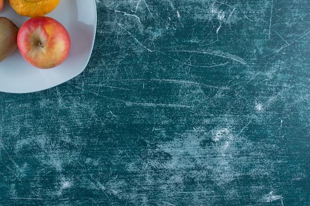 Мандарин, киви и яблоки на тарелке, на мраморном столе.