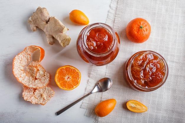 Tangerine and kumquat jam in a glass jar on whitewood