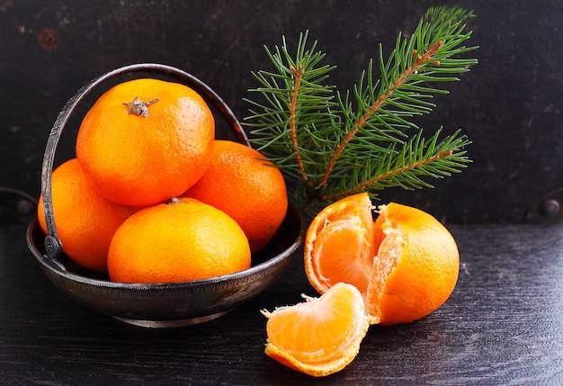 Tangerine in a metal basket with a branch of a christmas tree on a black background
