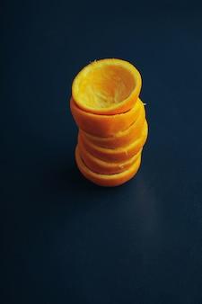 Il mandarino pelato copre la copertura dalla vista dall'alto a forma di colonna piramide isolato sul vecchio tavolo blu rustico vintage