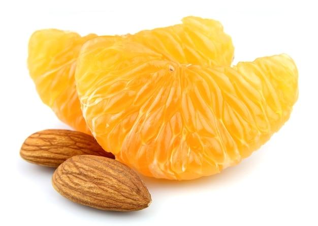 Долька мандарина с орехами на белом фоне