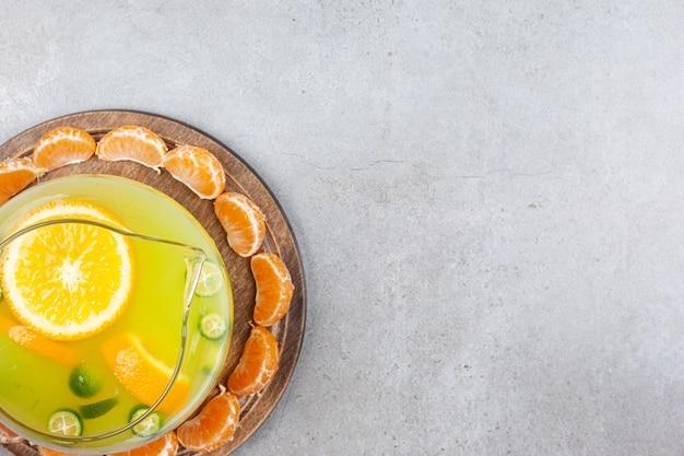 Tangerine slices around of fresh citrus lemonade on wooden tray over grey table.