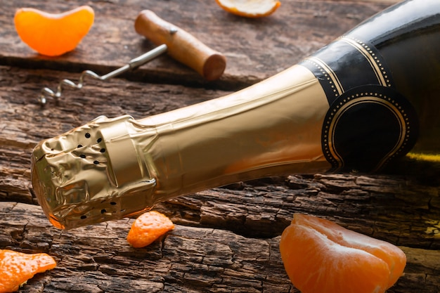 Tangerine slices near the champagne and a corkscrew on a wooden table