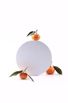 Tangerine on a white round podium. soft selective focus. winter festive background.