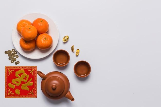 Tangerinea near teapot and cups