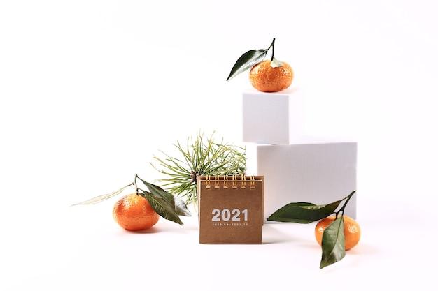 귤과 가문비나무 가지, 2021년 달력, 흰색 배경에 있는 편지. 크리에이티브 스칸디나비아 미니멀리즘 크리스마스 콘서트