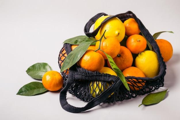 섬유 가방에 귤과 레몬. 건강에 좋은 음식과 제로 폐기물 개념.