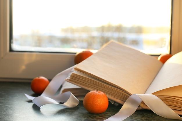 冬の窓際の大理石のテーブルにタンジェリンとヴィンテージの本
