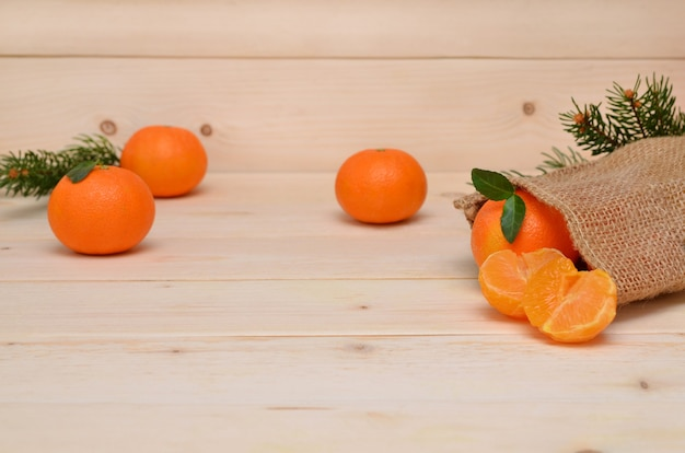 Tangerines fall out of the bag on the wooden table, place for object