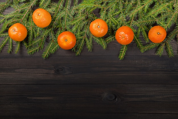 Tangerines on fir tree branches on dark wooden