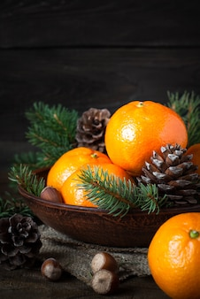 Tangerines, fir tree, pinecones and nuts. christmas food decorat