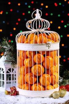 빛나는 배경에 크리스마스 장식으로 장식 새장에 감귤