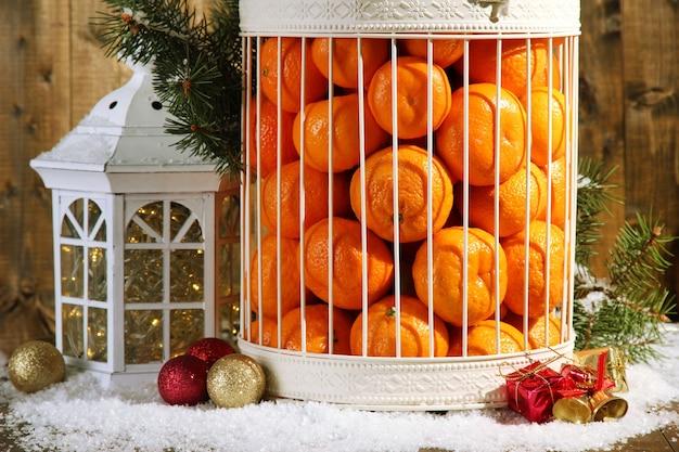 나무 배경에 크리스마스 장식이 있는 장식용 새장에 있는 귤