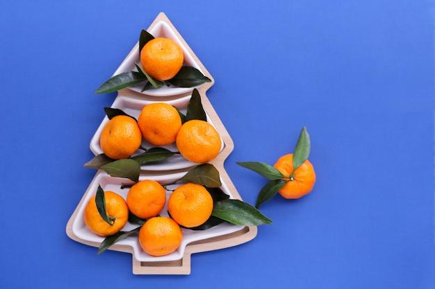 파란색 배경에 크리스마스 트리 모양의 귤. 크리스마스 음식 배경, 평면도. 재미있는 식용 크리스마스 트리