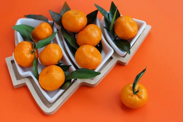 オレンジ色の背景にクリスマスツリーの形をしたみかん。クリスマス料理の背景、上面図。楽しい食用のクリスマスツリー