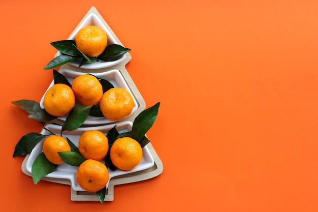 오렌지 배경에 크리스마스 트리 모양의 귤. 크리스마스 음식 배경, 평면도입니다. 재미있는 식용 크리스마스 트리.