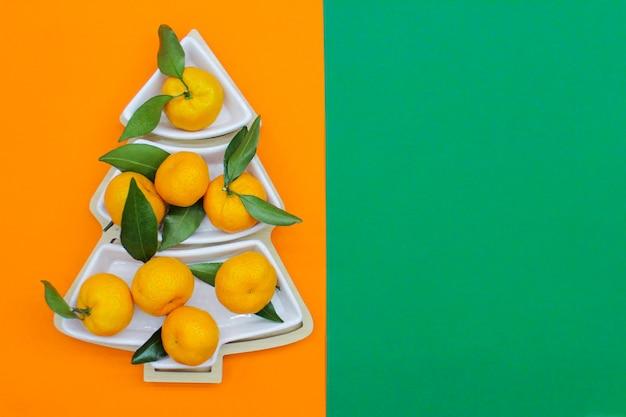 오렌지 녹색 배경에 크리스마스 트리 모양의 귤. 크리스마스 음식 배경, 평면도입니다. 재미있는 식용 크리스마스 트리.