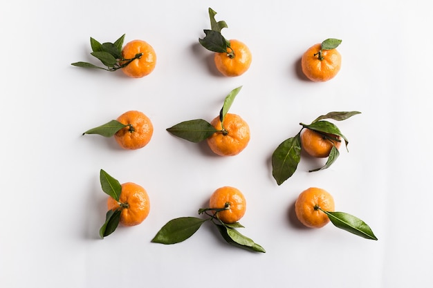 Tangerines isolated with green leaves on white