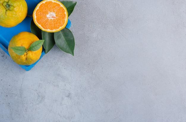Mandarini e foglie su un piccolo piatto blu su fondo di marmo.