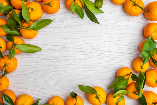 Tangerines mandarin with green leaves on a light wooden background. top view. copyspace