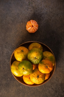 Tangerines or mandarines in bamboo bowl and ripe one on wooden background top view vertical orientation