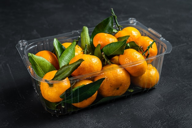 Tangerines, mandarines in a plastic container, box. black background. top view