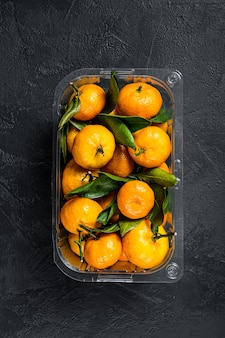 Tangerines, mandarines in a plastic container from the supermarket.