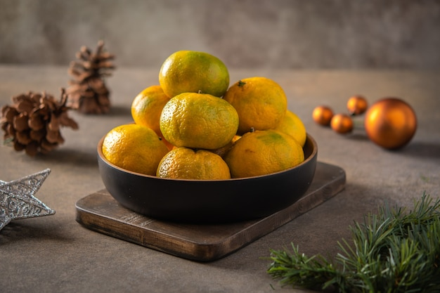 Tangerines or mandarines and ripe slices in bamboo bowl on wooden board, next to christmas tree branch, cones and toys