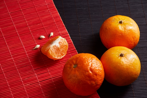 Tangerines mandarins, clementines, citrus fruits on style black and red surface with copy space