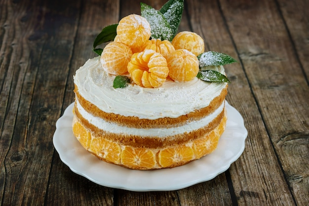 Tangerines naked cake with leaves on rustic background.