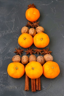Tangerines, nuts and anise in the shape of a christmas tree on dark background