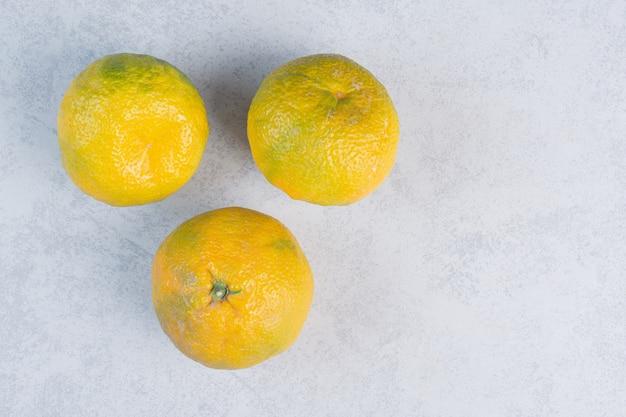 Tangerines (oranges, clementines, citrus fruits) over grey background .