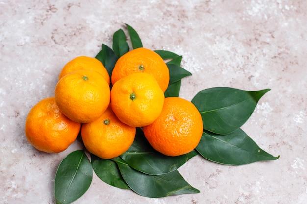 コピースペースとコンクリートの表面に緑の葉とみかん(オレンジ、クレメンタイン、柑橘類)