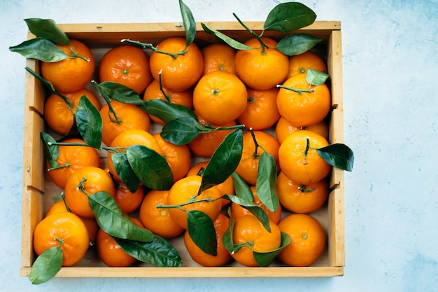 Tangerines oranges, clementines, citrus fruits with green leaves in a wooden box over light  with copyspace