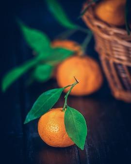 みかん、オレンジ、みかん、クレメンタイン、柑橘系の果物、素朴な木製の暗い背景の上にバスケットの葉、コピースペース。
