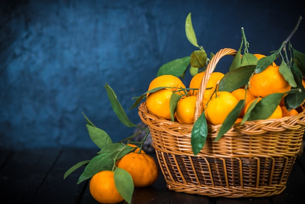 Мандарины, апельсины, мандарины, клементины, цитрусовые, с листьями в корзине над деревенской деревянной темной